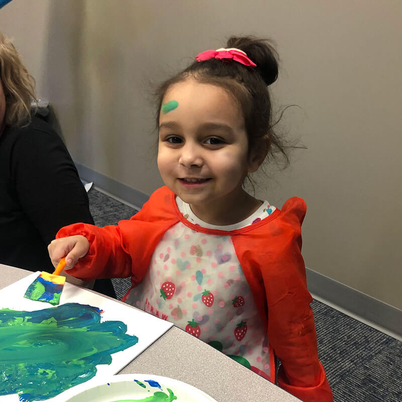 Girl with autism painting blue and green picture.